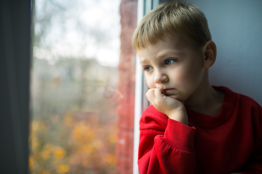 Young boy with blonde hair sitting and looking out the window sadly with his head in his hand.